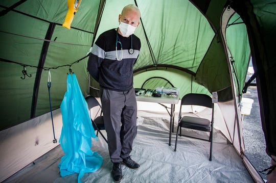 Medical practitioner and Airforce veteran Travis Newman manages a coronavirus testing tent outside of the American Health Network facility on Morrison Road Tuesday.