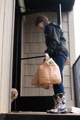 FiftyForward Executive Director Sallie Hussey delivers groceries to Bonnie Peters, at her home Tuesday, March 24, 2020, in Nashville, Tenn.