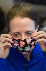 Hope Dillard tries on one of the masks she made with her mom and sister to help in the fight against the coronavirus in  Carthage, Tenn. Monday, March 23, 2020.