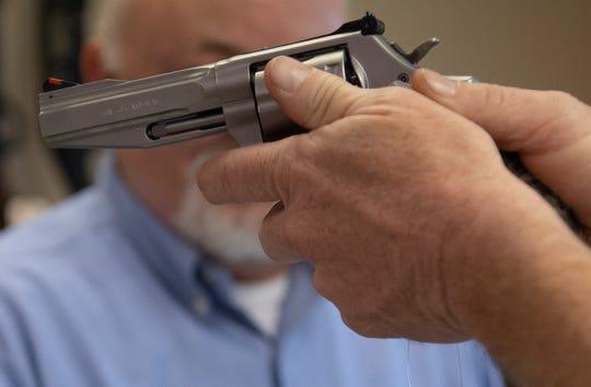 Smyrna Guns customer Doug Timmons handles a revolver as he shops for a handgun Tuesday, March 24, 2020 in Smyrna, Tenn.