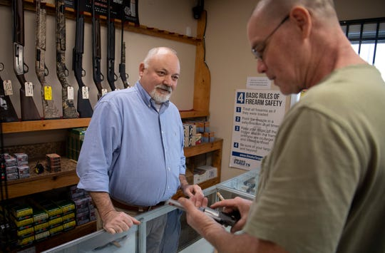 Smyrna Guns manager Richard Boone assists customer Doug Timmons as he shops for a handgun  Tuesday, March 24, 2020 in Smyrna, Tenn.