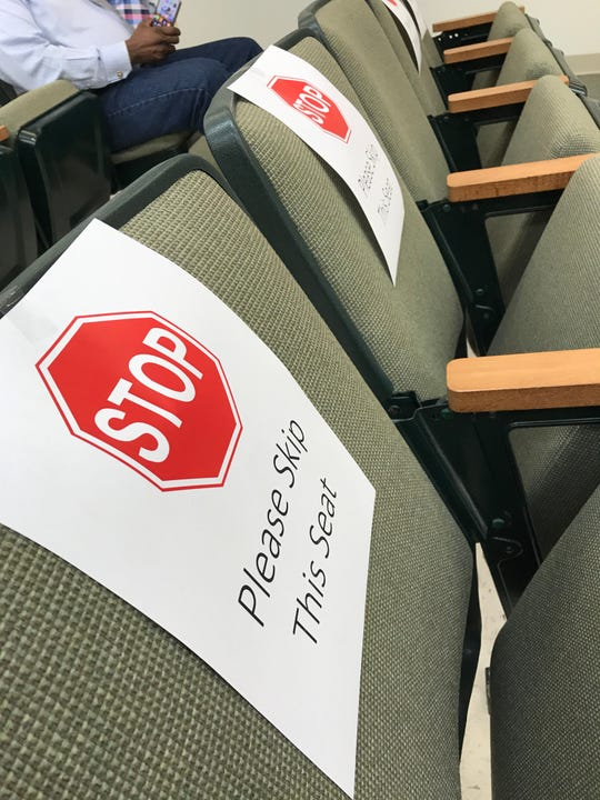 Signs sitting on seats in the Dickson Council chambers to ensure proper spacing of audience members.