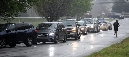 Freedom Middle School parents line up in their cars to pick up student learning packets in Franklin on Tuesday, March 24, 2020.