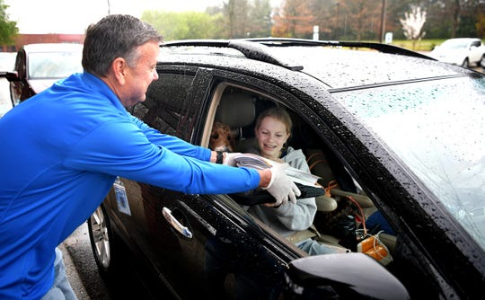 FSSD Director of Schools Dr. David Snowden hands out student learning packet to Freedom Middle School seventh grader Sophia Taylor during a drive-thru pickup line at the Freedom Middle School in Franklin on Tuesday, March 24, 2020.