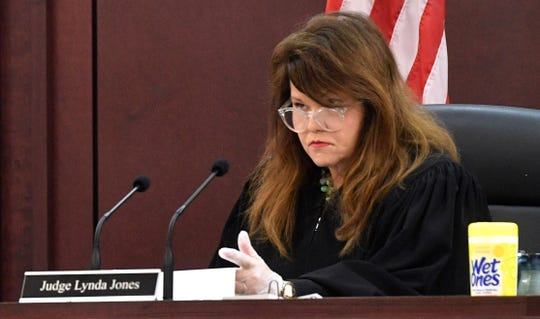 Judge Lynda Jones now only has a skeleton crew and allows only 10 people in court at a time. She is also now wearing protective gloves as she handles paperwork and has wipes close by in Nashville, Tenn. Tuesday, March 24, 2020.
