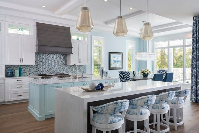 Chrissy Howard and  Janine Blume continued the home's coastal style indoors with warm oak floors, white shaker kitchen cabinets and white quartz countertops with a royal blue and aqua glass tile backsplash.