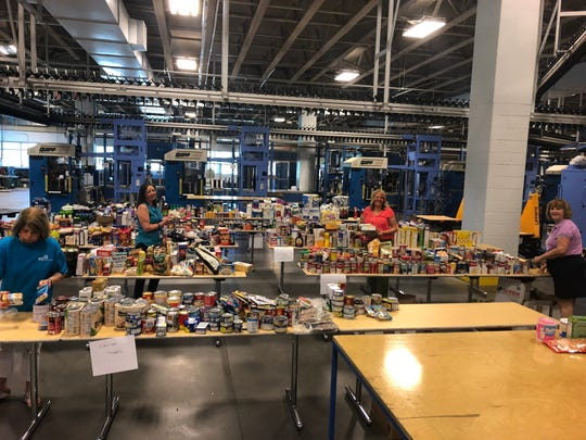 Naples Daily News workers sort more than 7,000 pounds of food collected in this year's Satisfy The Hunger campaign. The newspaper began the annual campaign in 2016.