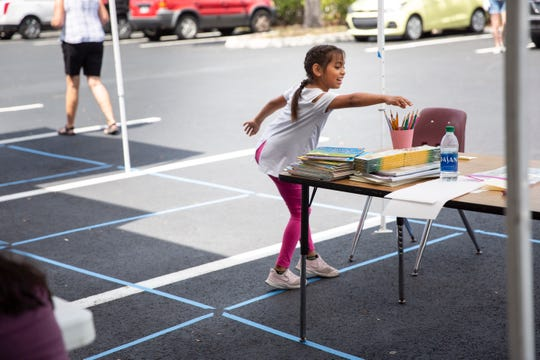 Joselyn Carapia reaches for a colored pencil while trying to stay on the blue line for social distancing at Gargiulo Education Center in North Naples on Tuesday, March 24, 2020.