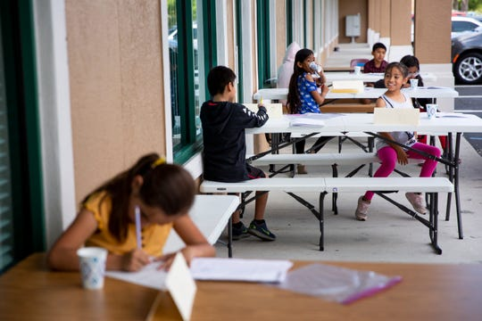 Students sit six feet apart from one another on opposite sides of the table as they work on educational packets at Gargiulo Education Center in North Naples on Tuesday, March 24, 2020.
