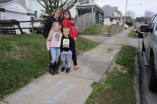 Janet Wheatley and her grandchildren, Lainee Whealty, Madison Pebbles and Kingston Walker, chalked words of encouragement to lift the spirits of those in their neighborhood on Sunday.
