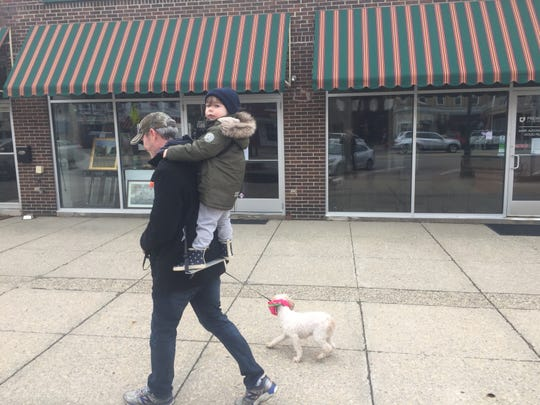 Stuart Bryan and son St John, age 3, walk with their dog, Ghost, through a mostly empty downtown Granville on March 24.