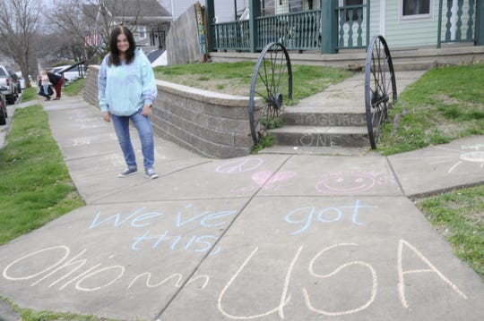 Lori Holdren looks at the encouraging messages she left for her neighbors with the help of her husband Dave, son and daughter-in-law, Bear and Kayla Holdren and grandson Maxton on Sunday.