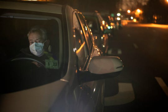 John Dougherty of Bloomfield waits at 3:12 a.m. outside of the entrance to Bergen Community College, where a drive-thru coronavirus testing center will open at 8 a.m. on Tuesday, March 24, 2020.