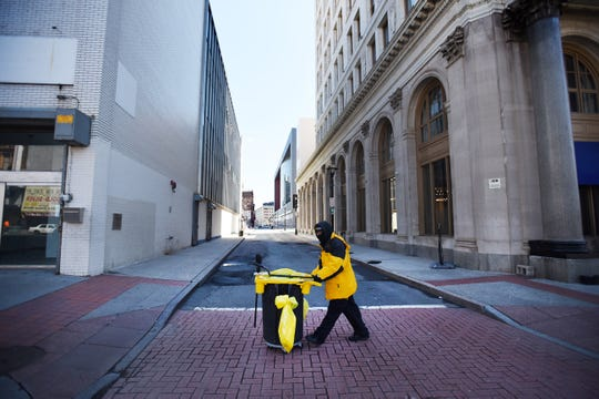 A lone city worker pushes a garbage bin along Broad Street in Newark, NJ on Tuesday March 24, 2020.
