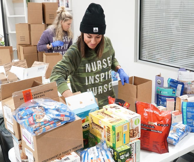 Nurses Inspire Nurses founder Cat Golden, right, a former practicing RN, and nursing student Mackenzie Lago put together care packages at their Plymouth location on March 24, 2020.