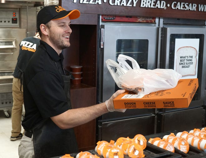 Little Caesars franchisee Daniel Wanshon brings a customer's order out on March 24, 2020 at his Canton Center restaurant.