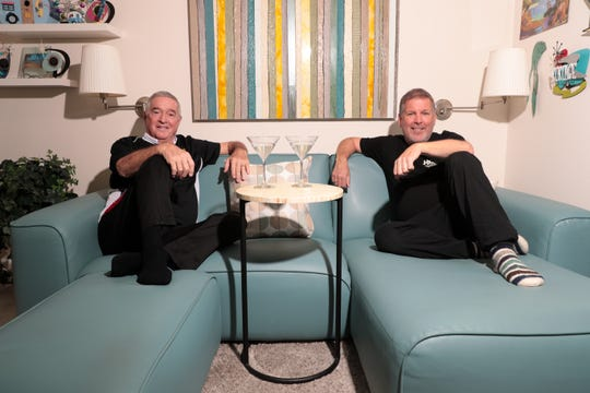 """David Carden Jr., left, and Dale Maguire, right, sit in their newly decluttered den on Tuesday, March 24, 2020, in Palm Springs, Calif., enjoying a """"Quarantini"""" after a hard day's work."""
