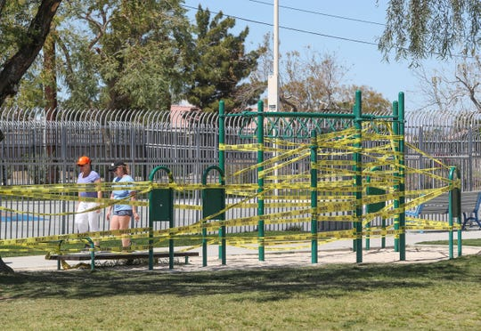 Walkers in La Quinta Park pass exercise equipment which has been taped off and closed by the City of La Quinta in response to the coronarvirus, March 24, 2020.