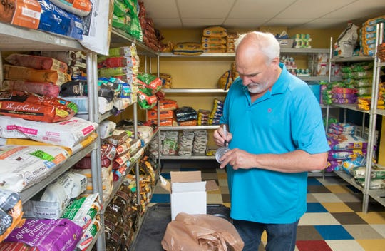 John Cheney processes a recent donation at the 400 Paws pet food pantry on Creighton Road in Pensacola on Tuesday. The pantry plans to continue handing out pet food to low-income families  on the fourth Sunday of every month during the coronavirus pandemic.