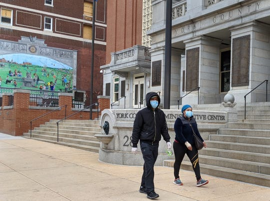 Two people walk past the York County Administrative Center in York wearing masks against the backdrop of a Rotary Club anniversary mural of people frolicking in a park.