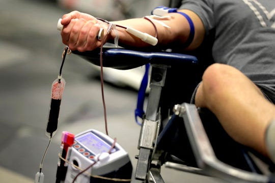James Kershaw donates blood at a temporary blood bank set up in a church's fellowship hall Tuesday, March 24, 2020, in Tempe, Ariz. Schools and businesses that typically host blood drives are temporarily closed due to precautionary measures in place to reduce the spread of the COVID-19 coronavirus leading to extremely low levels of blood availability throughout the state.