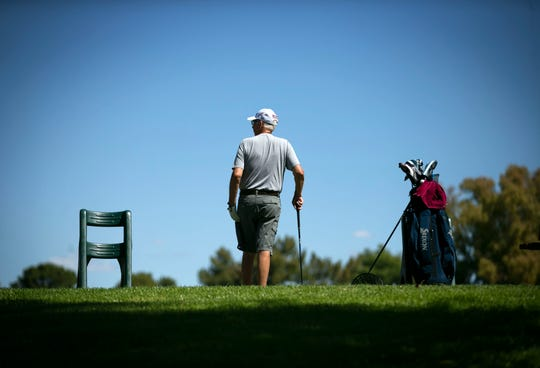 A man drives gold balls at the driving range at BellAir Golf Course in Phoenix on March 24, 2020. Most golf courses in Arizona have remained open during the coronavirus pandemic.