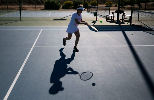 Katherine Negrete of Peoria, plays tennis at Paseo Racquet Club in Glendale on March 24, 2020. Paso Racquet Club is telling guests to only play on every other court to spread people out because of the coronavirus. Paseo Racquet Club says their business is down by 50 percent for this time of year because of coronavirus despite being one of the few athletic and fitness facilities still left open.