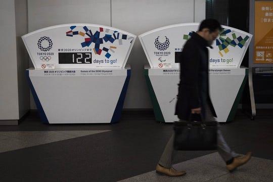 Un individuo camina frente a un despliegue de la cuenta regresiva de los Juegos Olímpicos de Tokio 2020.