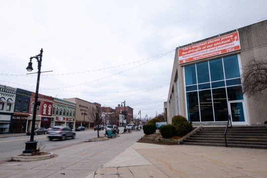 A banner with an inspirational message asking passersby to support local businesses through the coronavirus pandemic hangs on the Michigan Mutual building Tuesday, March 24, 2020, in downtown Port Huron.