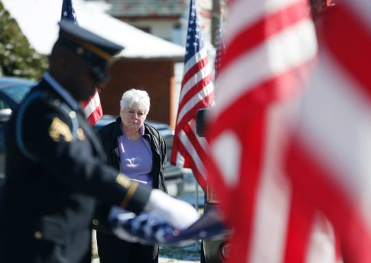 Stuart Vidal's widow Noel McCaffery watches from a distance as New Jersey Army National Guard first sergeant Gregory Williams folds the flag that draped Stuart's casket during his funeral service at Poughkeepsie Rural Cemetery on March 24, 2020.