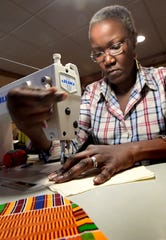 Gusa by Victoria owner Victoria Kageni-Woodard, sews face masks at her York City shop Tuesday, March 24, 2020. She and her three children were making the masks which are being distributed locally and abroad due to a shortage amid the Covid-19 virus pandemic. She said she expects to make 100 per day. Bill Kalina photo