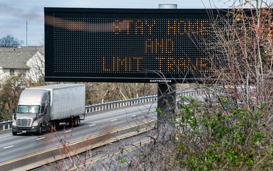 A truck rolls south on Interstate 83 while an electronic state warning sign tells drivers to 'STAY HOME AND LIMIT TRAVEL'. Truckers are among those considered essential for business so remain on the job.