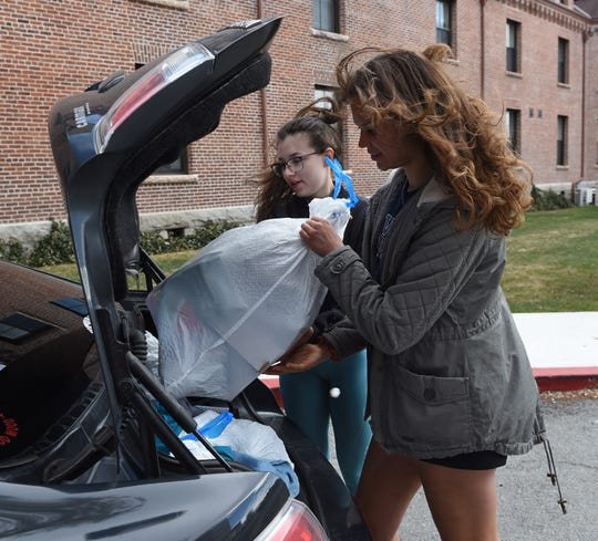 UNR students Ellyauna Stephenson, left, and Jadyn Carrier look to fit another bag in trunk of their car while moving out of the Juniper and Manzanita Hall on Monday March 23, 2020. Both student are going back home to Las Vegas.