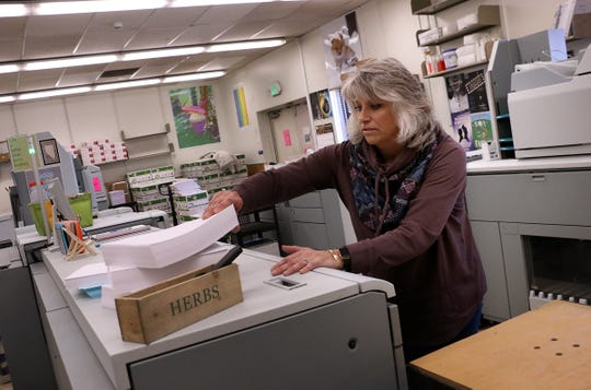 WCSD print shop employee Julie Smith helps to prepare school work packets for students without access to the internet on March 24, 2020.