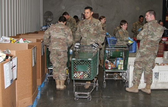 California National Guard soldiers work at a Sacramento County food bank as part of a humanitarian mission.