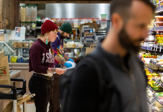 LifeSource harvester Chandra Timm shops for customers placing online orders at LifeSource Natural Foods in Salem, on March 23, 2020. Timm is in her first week as a harvester, hired in direct response to the coronavirus pandemic.