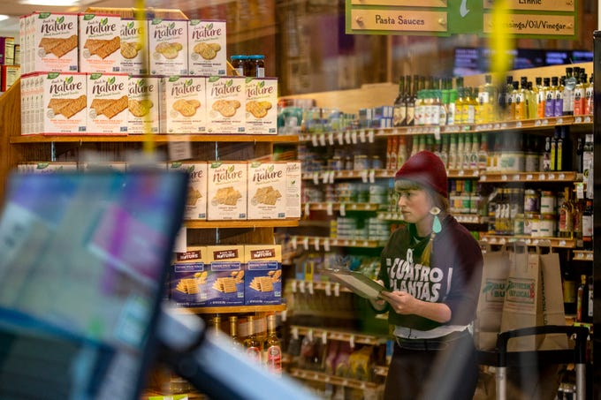 LifeSource harvester Chandra Timm shops for customers placing online orders at LifeSource Natural Foods in Salem, on March 23, 2020. The store has installed dividers at each register to limit customer and employee contact.