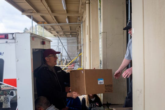 Norm Auzins, immediate past president of the Multnomah Dental Society and the Oregon Society of Oral and Maxillofacial Surgeons, helps unload personal protective equipment collected by the Oregon Dental Association at the Department of Corrections in Salem, on March 24, 2020.