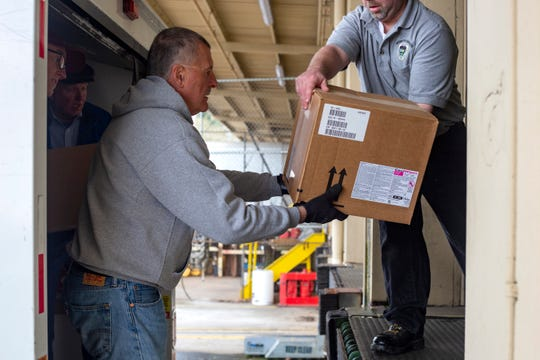 Jim Mattsen unloads personal protective equipment donated to the state of Oregon by the Oregon Dental Association at the Department of Corrections in Salem, on March 24, 2020.