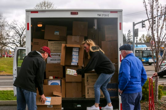 "Norm Auzins, Lora Mattsen, and Dennis Nicola help load protective equipment donated by regional dentists into a U-Haul in Salem, on March 24, 2020. ""Our dentists are giving away the inventory they don't know if they'll be able to get back again,"" Nicola, President of the Multnomah Dental Society, said."