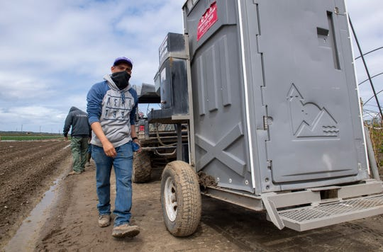 A fieldworker walks towards the portable restroom as he finishes washing his hands on March 24, 2020.