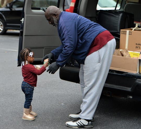Sylvester Bratten hands out chocolate milk during the COVID-19 outbreak on Tuesday, March 24, 2020.