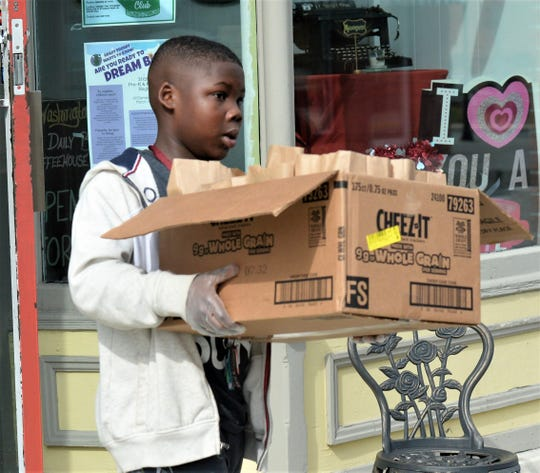 DaiJon Johnson helps deliver food to Snow Hill residents on Tuesday, March 24, 2020.