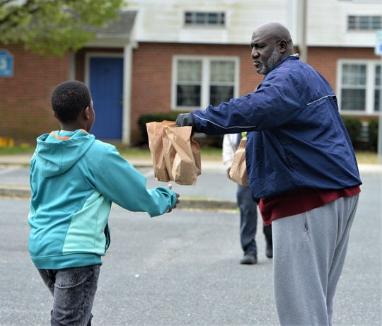 Sylvester Bratten and other volunteers hand out lunches to Snow Hill residents during the COVID-19 outbreak on Tuesday, March 24, 2020.