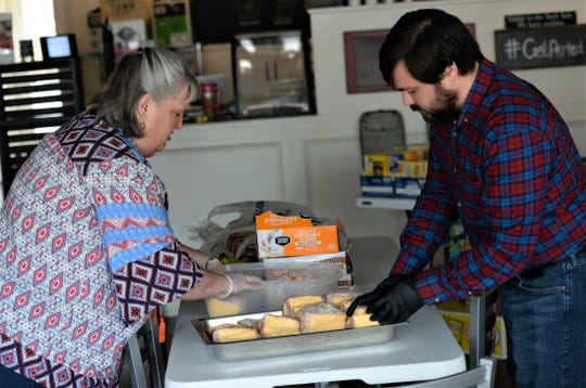 Pastors Joshua Berry and Mary Haggard helps prepare lunches to distribute to Snow Hill residents during the COVID-19 outbreak on Tuesday, March 24, 2020.