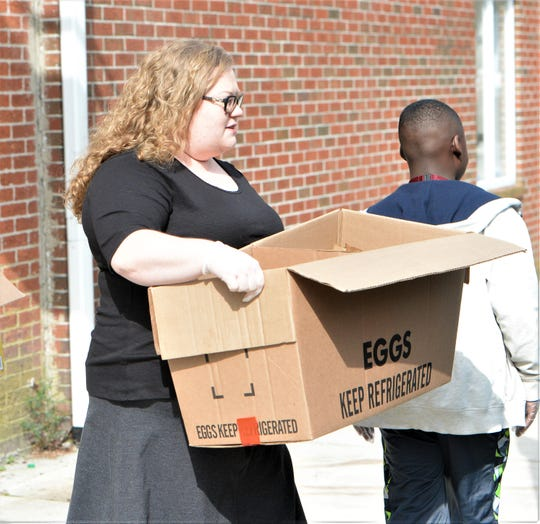 Lorissa McAllister helps distribute food to Snow Hill residents during the COVID-19 outbreak on Tuesday, March 24, 2020.