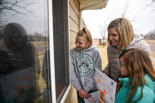 """Nealie Stanford, 10, Sara Stanford and Maesa Stanford, 7, visit with their """"Gigi"""" on Monday, March 23, 2020 at Edgewood Assisted Living in Sioux Falls."""