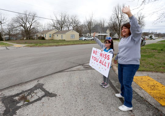 First-grader Haley Clayton and her mom Michelle Clayton wave at teachers from her school Robberson Elementary as the teachers drive in a parade to let their student know they miss them on Monday, March 23, 2020.