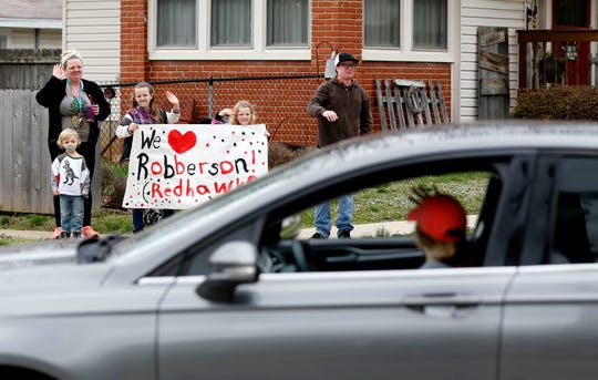 A family waves at teachers from Robberson Elementary as the teachers drive in a parade to let their student know they miss them on Monday, March 23, 2020.