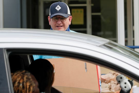 Volunteer Patrick Kennedy brings a box of food for two households from Second Harvest of the Big Bend to a car at Godby High School Tuesday, March 24, 2020.